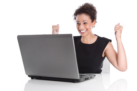 euphoric: Successful young business woman at desk with computer Stock Photo