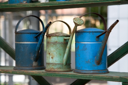 Three old watering pots outdoors photo