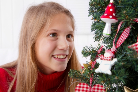 Waiting for the Christmas. Girl near the Christmas tree with decoration photo