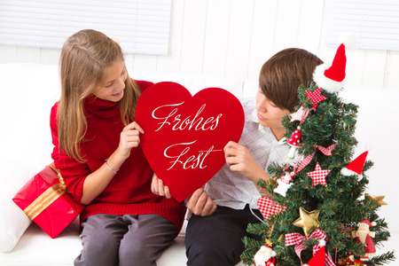 warmness: Children wish you Merry Christmas with heart decoration with sign