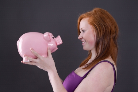 thrift box:  Redheaded girl dreams of future with savings in piggy bank
