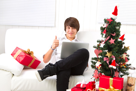 Boy on Christmas Eve with laptop thumbs up on couch photo