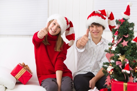 Cheerful kids under the Christmas tree with thumb up photo