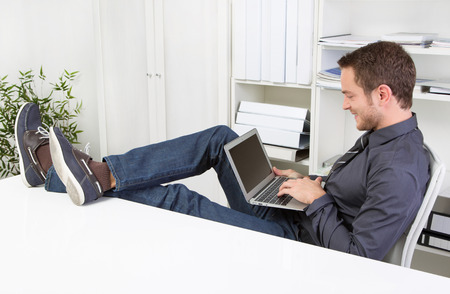 lunchbreak:  Man chatting during working hours with laptop at workplace