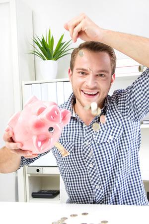 Pennies from Heaven. Business man with piggy bank at work. Standard-Bild