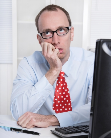 owe: Frustrated business man with tie and glasses at Office - thinking