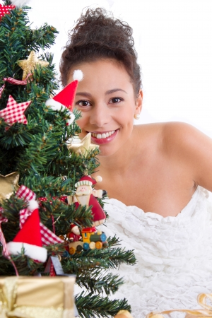 Happy lady behind the Christmas tree with decorations, isolated on white photo