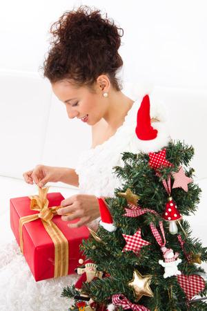 Beautiful woman unwraps christmas gift box, near the christmas tree, isolated on white Stock Photo - 24227242