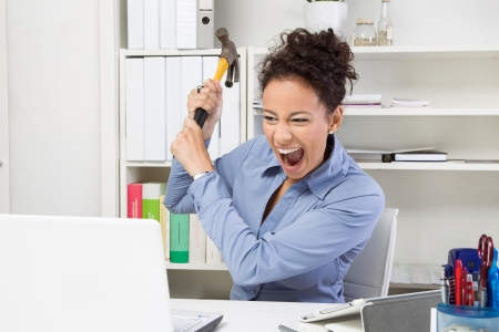 Faulty computer. Angry business woman with hammer want to crash laptop photo