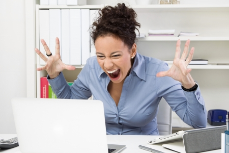 disgruntled: Outburst in the office. Angry business woman at workplace Stock Photo