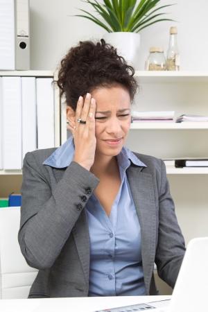 overburdened: Businesswoman having headache in the office Stock Photo