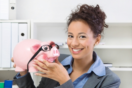 careerist: Smiling business woman with savings in piggy bank, at workplace
