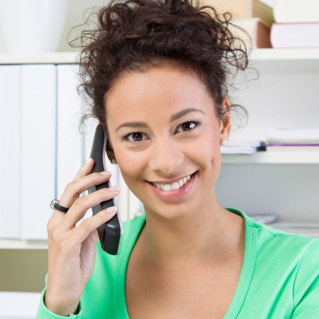 Smiling business woman on phone in office. photo