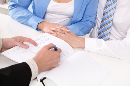 financial agreement: Hands - young married couple in a business meeting Stock Photo