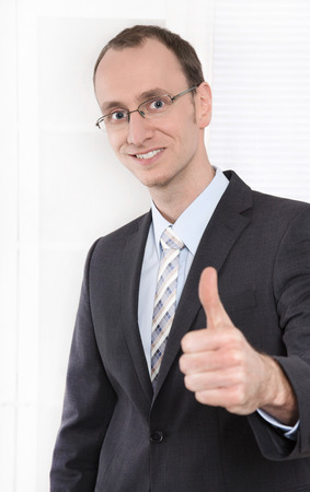 Successful businessman with suit and tie smiling and thumbs up at office - managing director