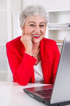 entrepreneurial: Portrait of older office worker with laptop
