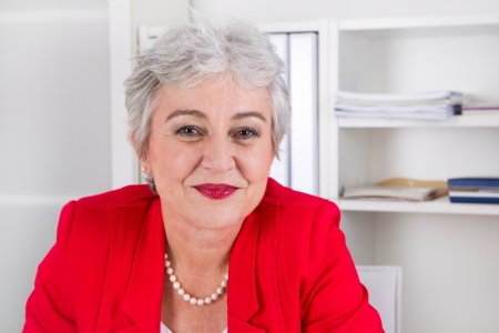 Portrait of senior expert in red at workplace