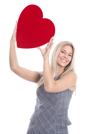 Happy young blond caucasian woman holding big red heart - love. photo