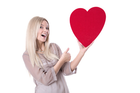 thump: Happy young blond caucasian woman holding red heart and thump up - love.