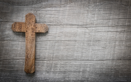Old wooden cross on a old wooden background with copy space for a condolence text. Imagens