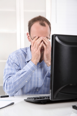 demotivated: Overworked businessman in shirt frustrated and stressed in his office with computer - overtime.