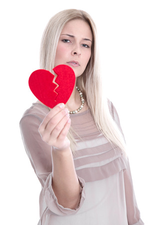 Sad blond caucasian woman holding broken red heart - love sickness. photo