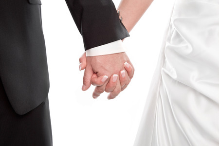 holding close: Isolated wedding couple holding hands