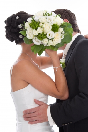 Kissing bride and groom hidden behind bride Bouquet isolated on White - marriage. photo