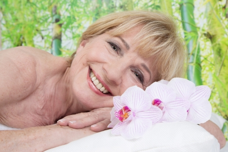 Relaxed elderly woman in spa is smiling photo