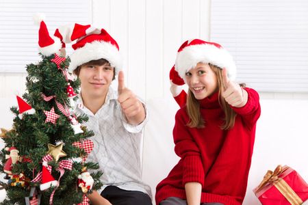 Cheerful children under the Christmas tree with thumb up photo