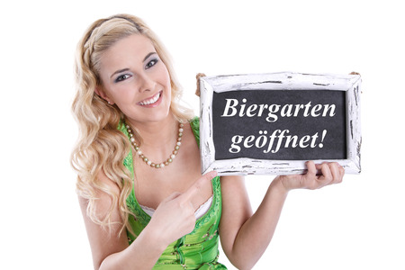 open country:  Beer garden is open in Bavaria at Oktoberfest  Bavarian woman holding sign, isolated on white