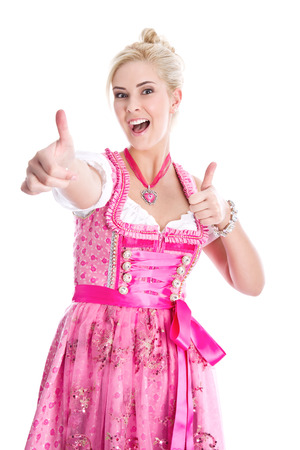 dirndl: Blond woman in Dirndl with thumbs up isolated in Pink Stock Photo