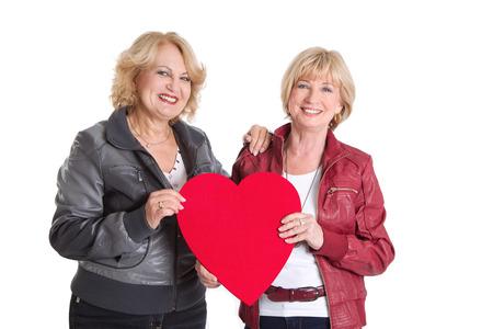 lesbians: Elder women standing with a big hear-shape for love or valentine