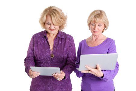 Two women standing with tablet and laptop - isolated on white photo