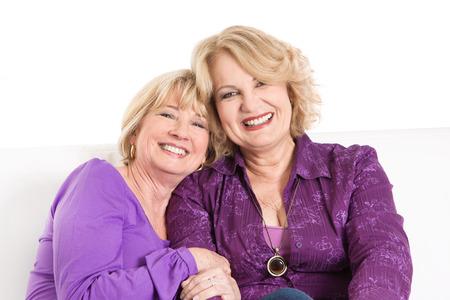 Portret van twee oudere vrouwen glimlachen in paars of violet shirts