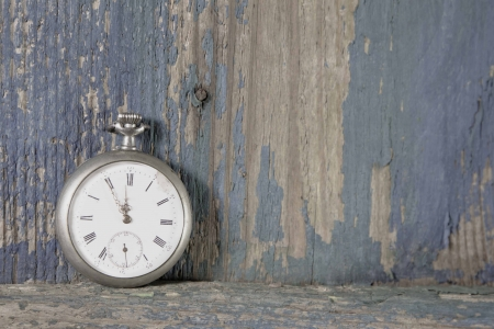 Old pocket watch on a rustic vintage wooden in shabby chic style