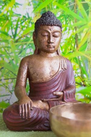 singing bowls: Buddha figurine on bamboo