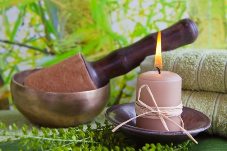 singing bowl massage: Asiatic singing bowl with a burning candle in a aromatic spa center Stock Photo