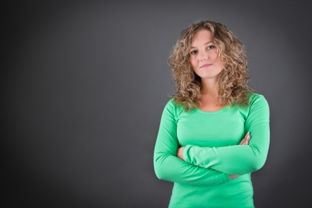 uniform curls: Young woman in a green shirt with crossed arms isolated on gray background