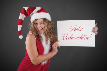 sexy costume: Happy woman in Santa hat holding Happy Christmas sign Stock Photo