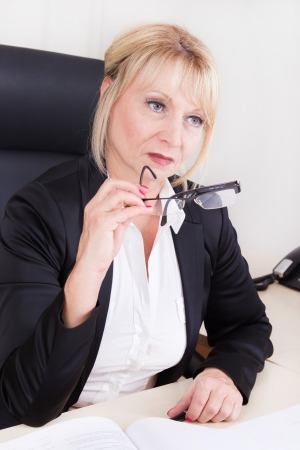 womanhood: Succesful businesswoman sitting in her office with glasses in her hand Stock Photo