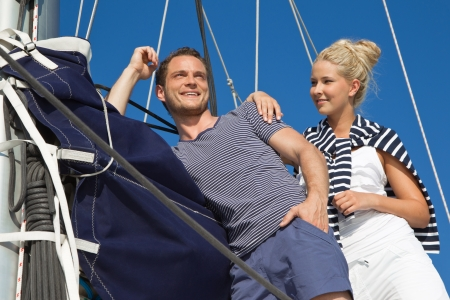 pleasure boat: Young couple in love making cruising holiday on a sailboat