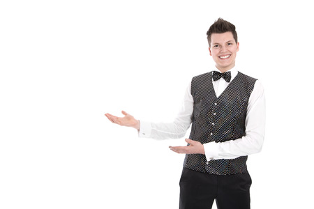 Isolated young smiling waiter or butler gesturing welcome  photo