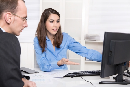 Two business people talking together at desk - adviser and customer or recruitment