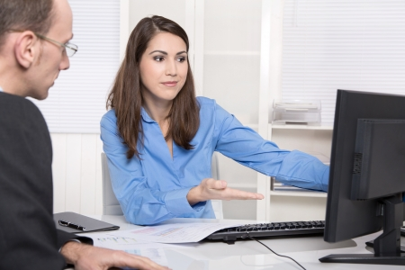 client service: Two business people talking together at desk - adviser and customer or recruitment Stock Photo