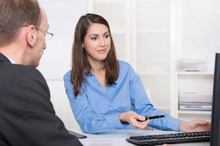 oficinista: Dos hombres de negocios hablando juntos en el escritorio - el asesor y el cliente o el reclutamiento