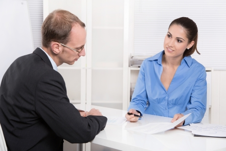 desk clerk: Two business people talking together at desk - adviser and customer or recruitment Stock Photo