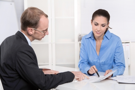 bank: Two business people talking together at desk - adviser and customer or recruitment Stock Photo