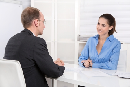 Two business people talking together at desk - adviser and customer or recruitment photo