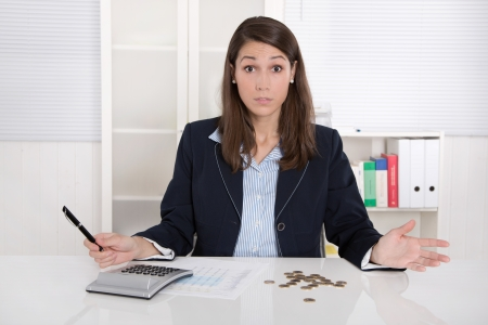 Disappointed business woman with euro coins in the office - empty cash